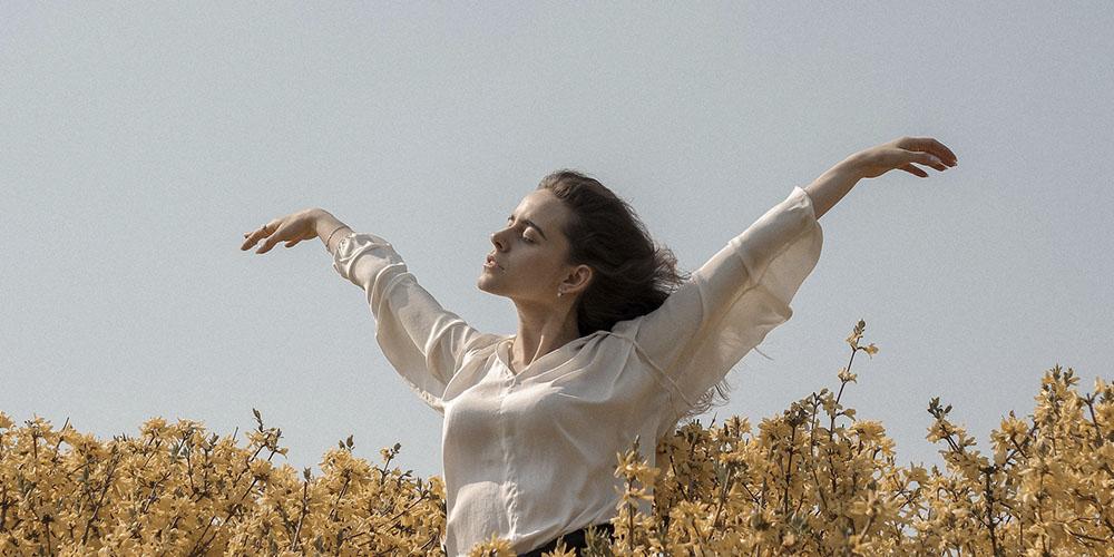 Mujer con los brazos abiertos disfrutando del viento