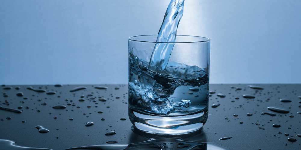 Vaso de agua llenándose bajo el chorro de agua